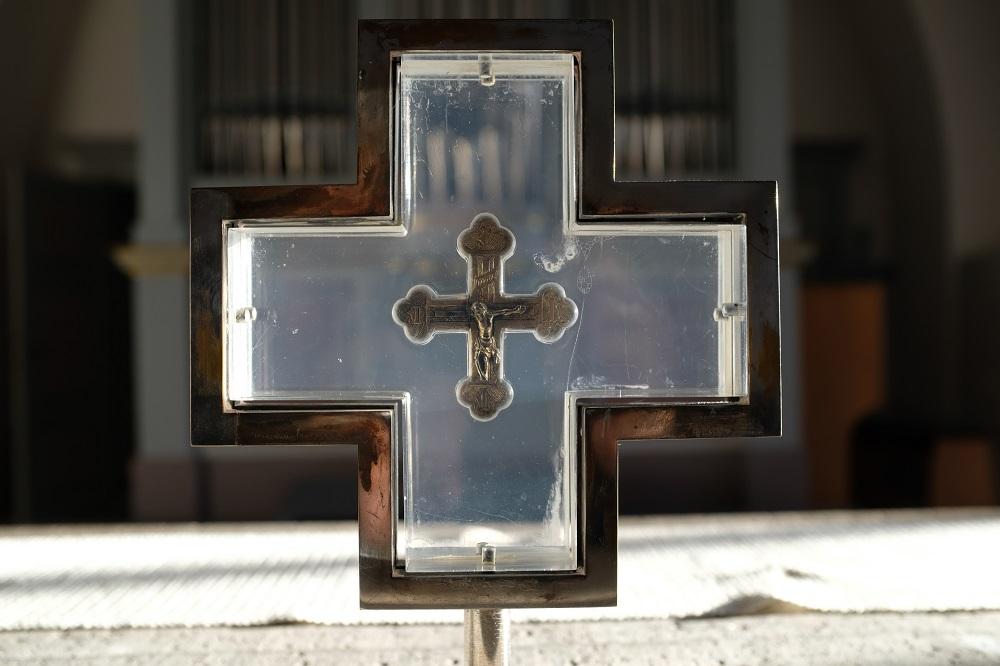 Ett krucifix i silver från 1400-talet i en ram av glas och metall.