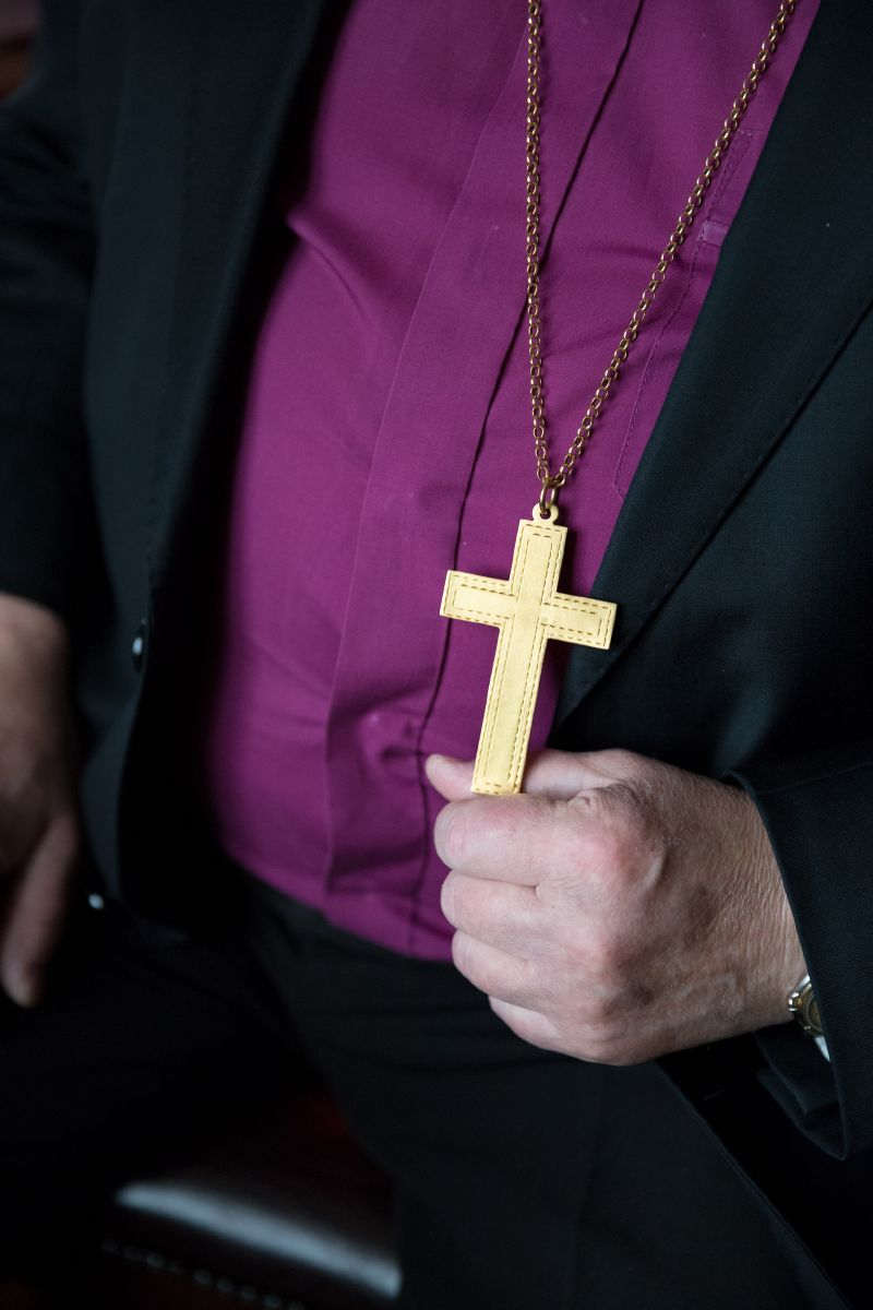 Biskop håller i sitt kors.