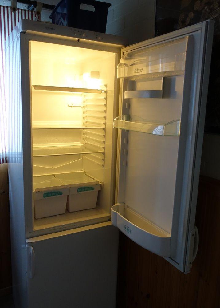 Ett tomt kylskåp med öppen dörr.