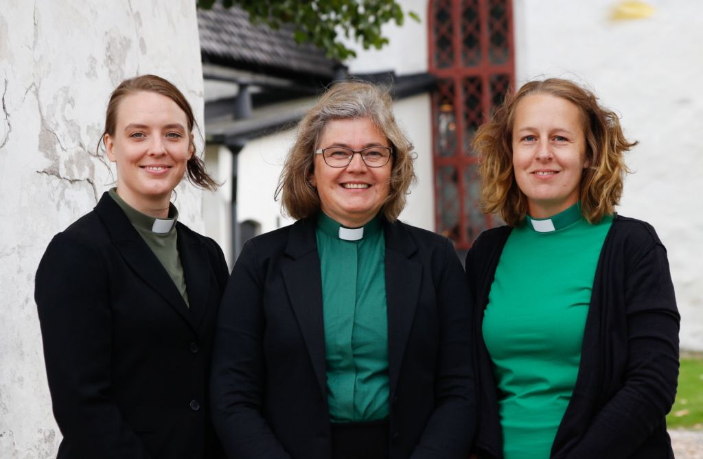 Tre diakoner i gröna ämbetsskjortor.