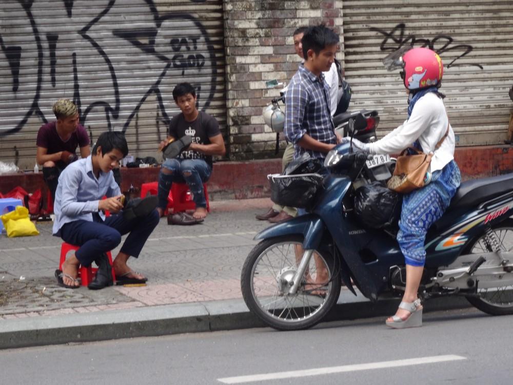 En kvinna på motorcykel på en gata utomlands.