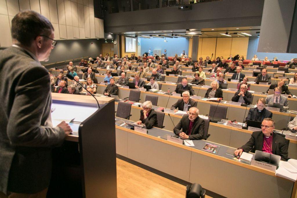 Människo rsitter i en sal och lyssnar på en föreläsare.