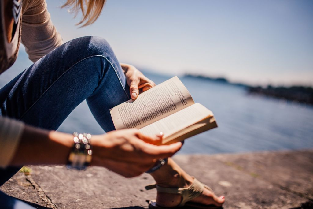 En person sitter i naturen och läser en bok