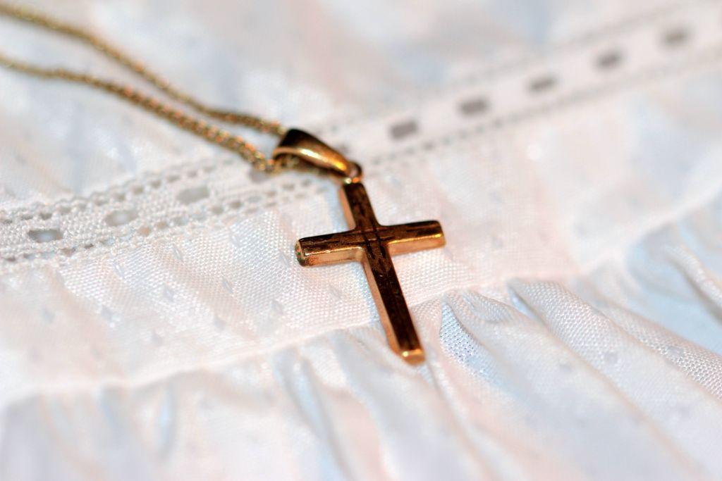 Ett guldkors på en dopsklänning