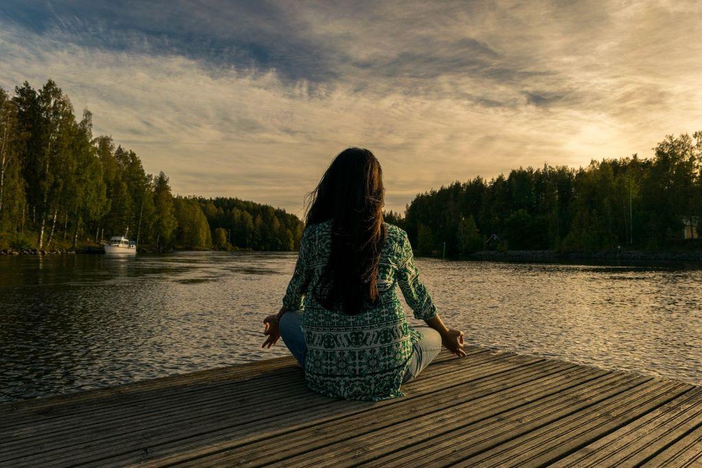 Kvinna på brygga i mediterande ställning